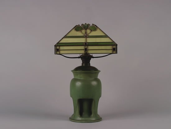 1247: A Teco Art Pottery Lamp with Leaded Glass Shade,