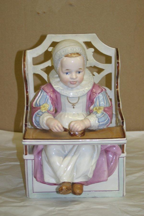 650: A Ceramic Figure Depicting a Child in a Highchair,