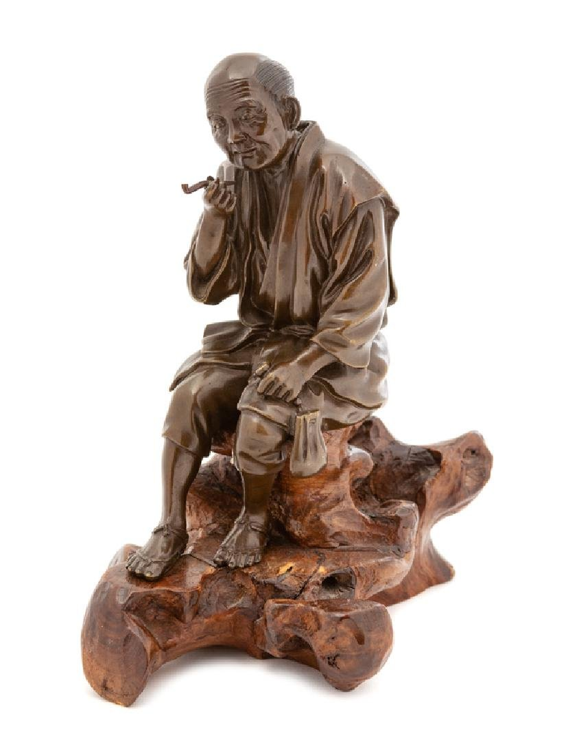 A Japanese Bronze of a Seated Man Smoking Pipe