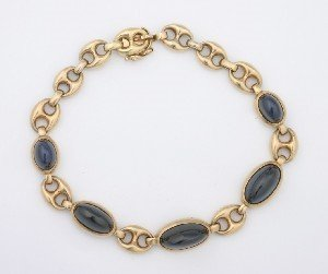 12: A Lady's 14 Karat Yellow Gold and Dark Blue Sapphir