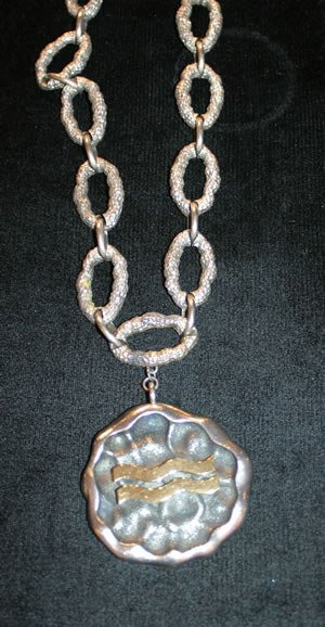 19: A Sterling Silver and Yellow Gold Zodiac Pendant, L