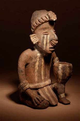 A Nayarit Terracotta Crouching Figure with Vessel