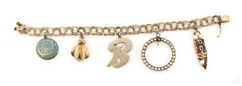 508: A 14 Karat Yellow Gold Charm Bracelet with Five Ch