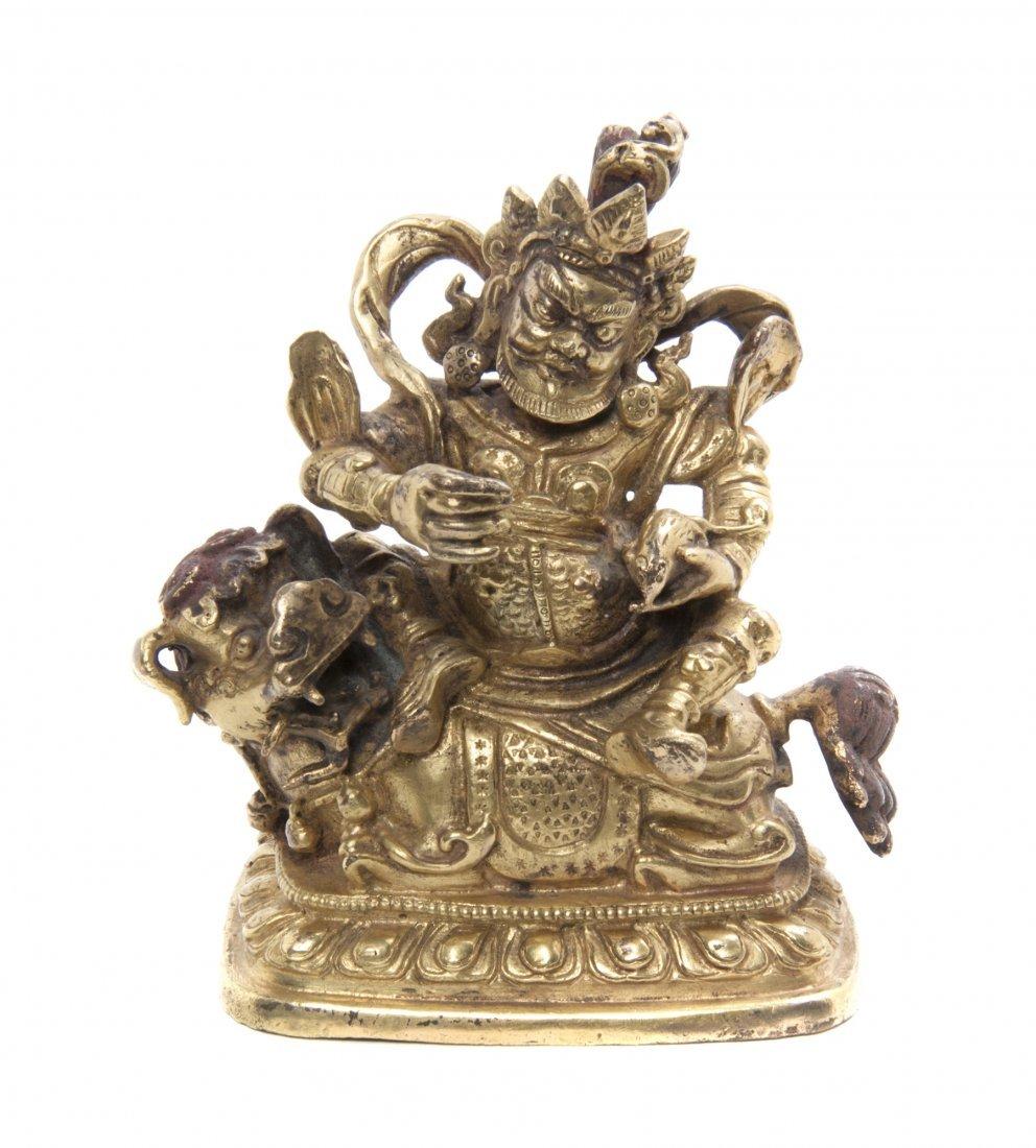 A Tibetan Gilt Bronze Figure Seated on a Qilin, Height