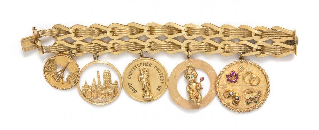 A 14 Karat Yellow Gold Charm Bracelet with Five Attache