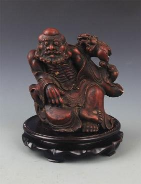 A BRONZE WITH MUD DHARMA FIGURE