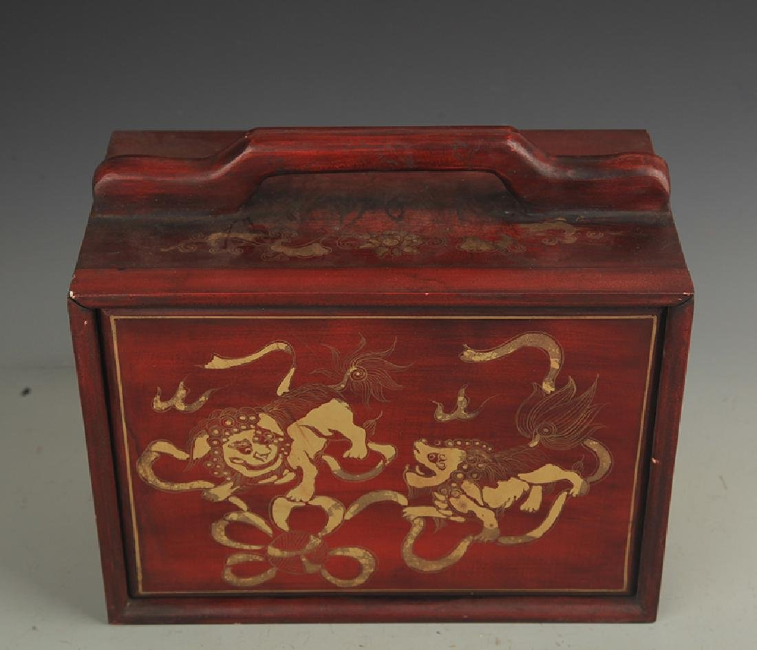 A GILT LACQUERED WOOD LION PLAYING LUNCH BOX