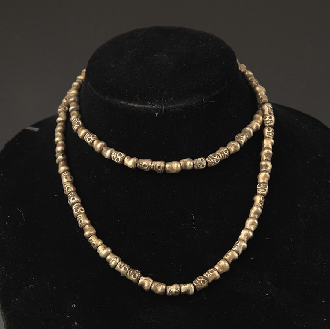 A FINELY CARVED BRONZE SKULL NECKLACE