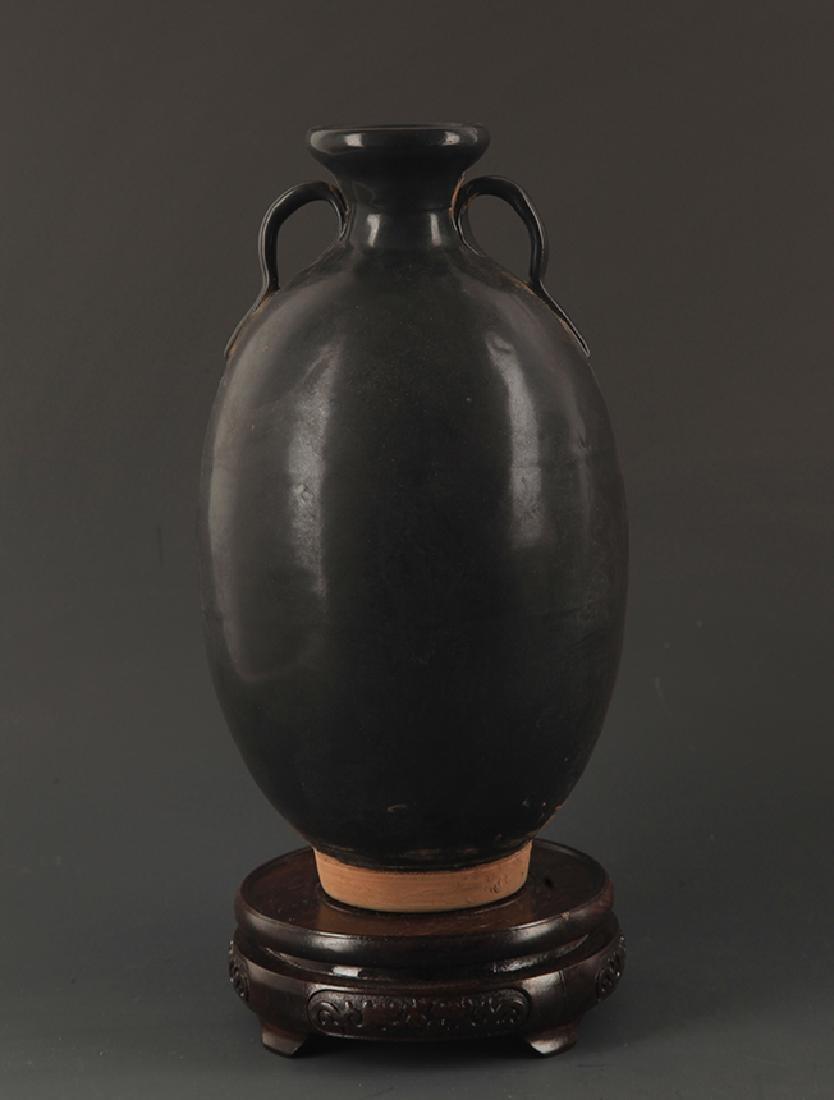 A BLACK GLAZED TWO TILE JAR