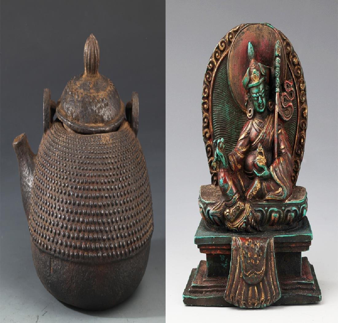AN OLD IRON TEAPOT AND TIBETAN BUDDHISM DECORATION