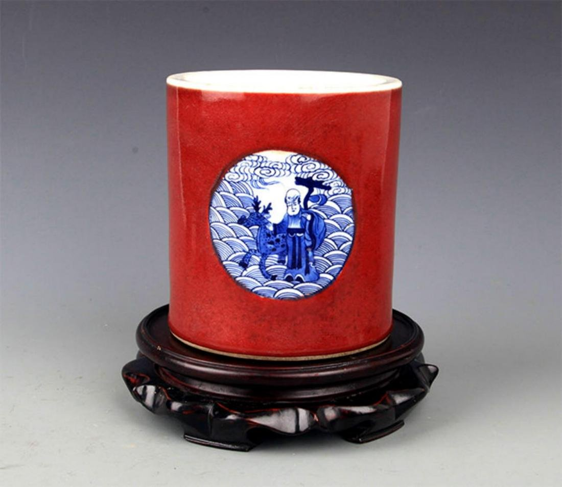 A RED GROUND BLUE AND WHITE BRUSH HOLDER