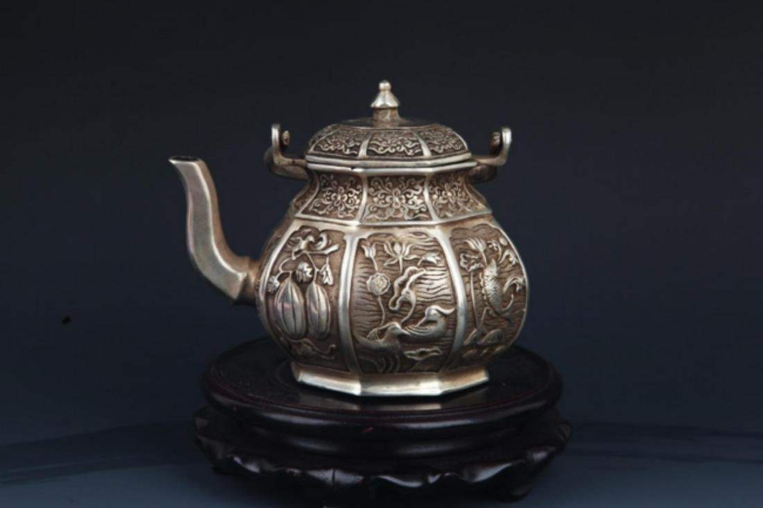 A FINELY CARVED SILVER PLATED BRONZE WATER POT