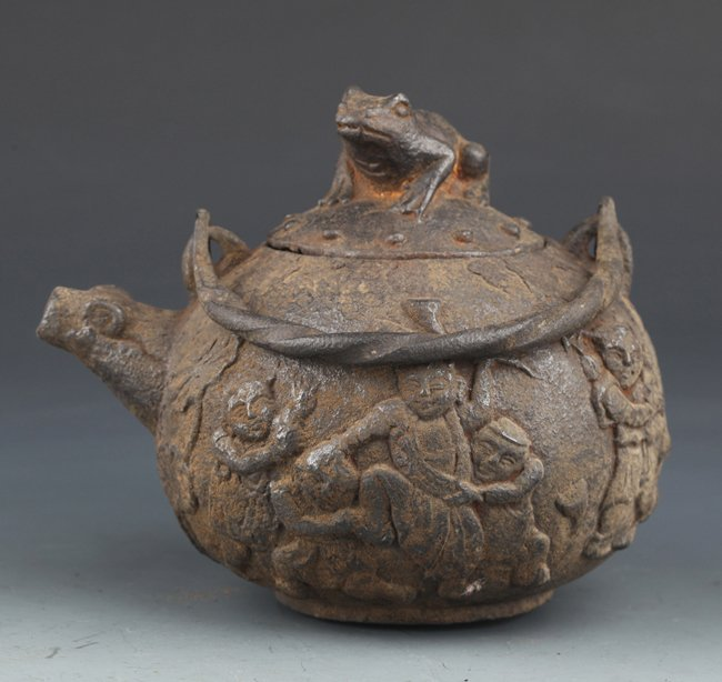 "AN UNUSUAL ""CHILDREN PLAYING"" CARVED IRON TEA POT"