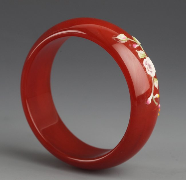 A RED AGATE BANGLE WITH FLOWER DESIGN