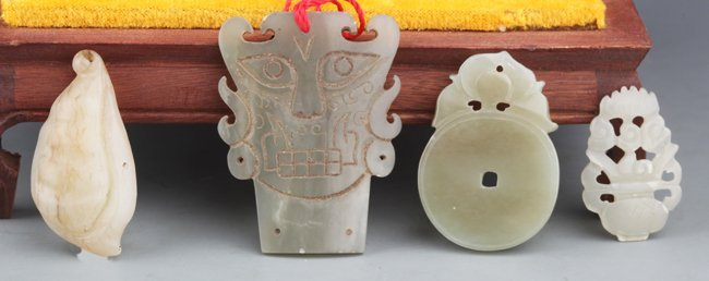 A GROUP OF FOUR FINELY CARVED GREENISH WHITE JADE