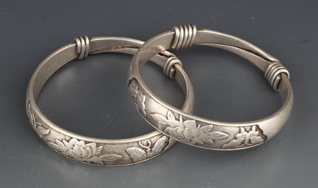 A PAIR OF FINELY CARVED SILVER PLATED BANGLES