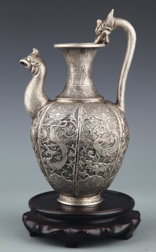 A FINELY CARVED SILVER PLATED WATER POT