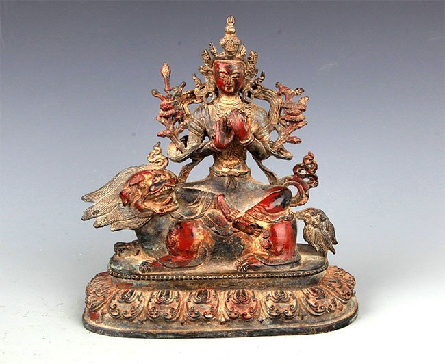 A BRONZE BUDDHA AND LION FIGURE