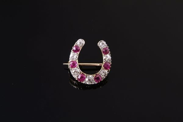 1021: A late Victorian ruby and diamond horseshoe brooc