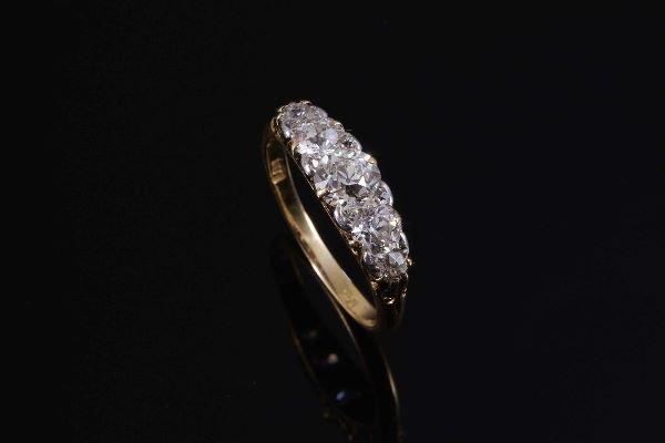 1043: A diamond five stone half hoop ring, the graduate