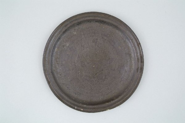 2218: A pewter plate, with hammered decoration of a sty