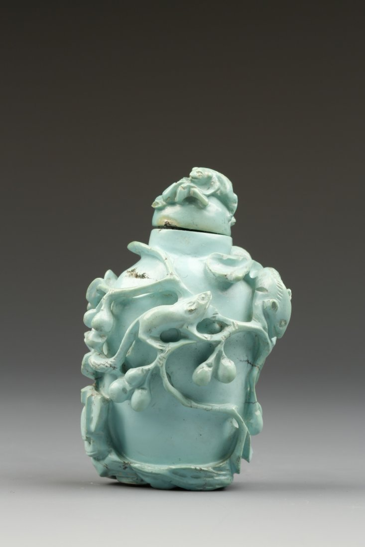 A TURQUOISE SNUFF BOTTLE carved in high-relief with squ