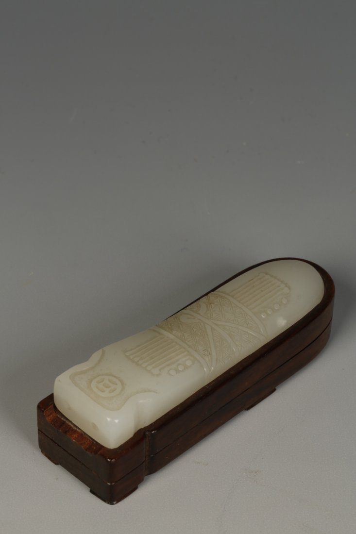 A PALE CELADON JADE PENDANT carved in the form of a qin