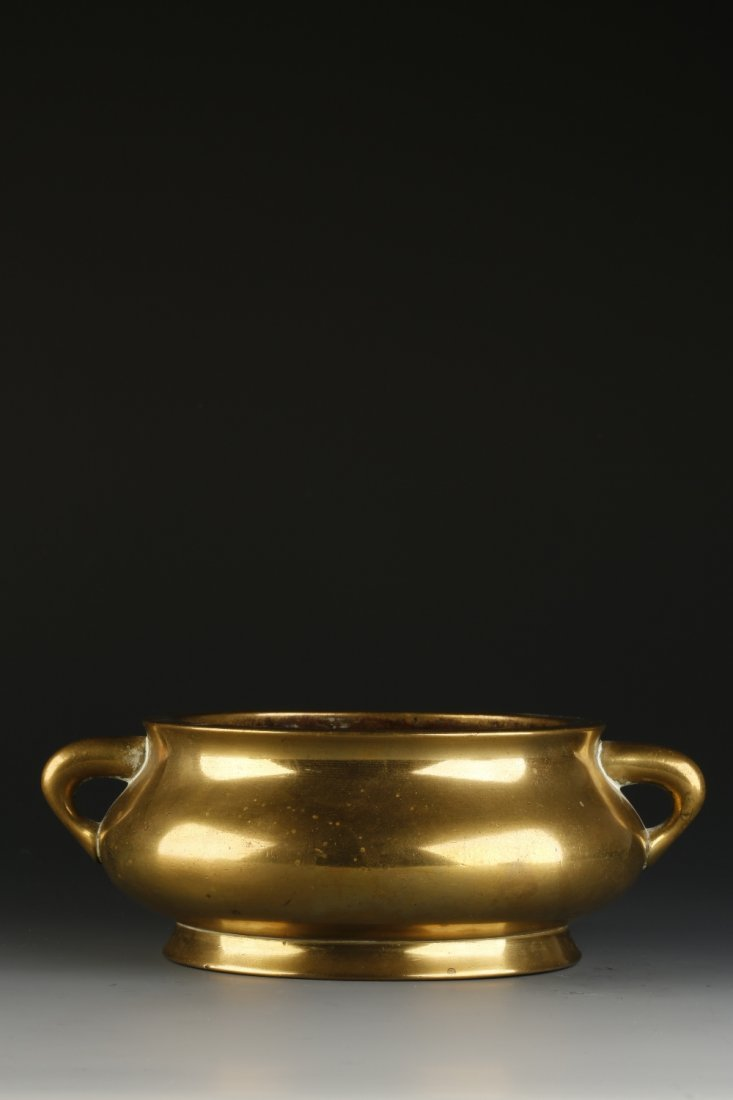 A BRONZE SQUAT CENSER with loop handles, the base with