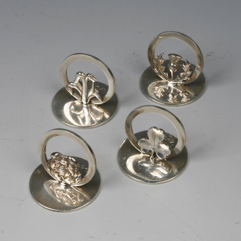 A SET OF FOUR MENU CARD HOLDERS with disc bases and hoo