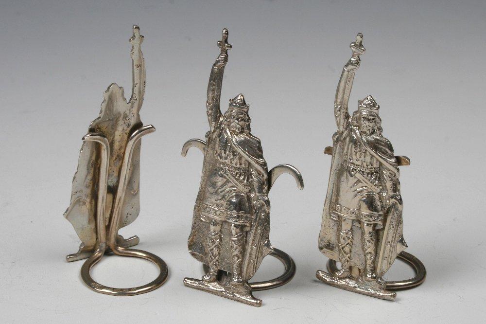A HARLEQUIN SET OF THREE MENU CARD HOLDERS modelled as