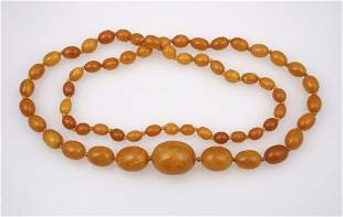 A GRADUATED ROW OF OVAL AMBER BEADS, knotted, the large