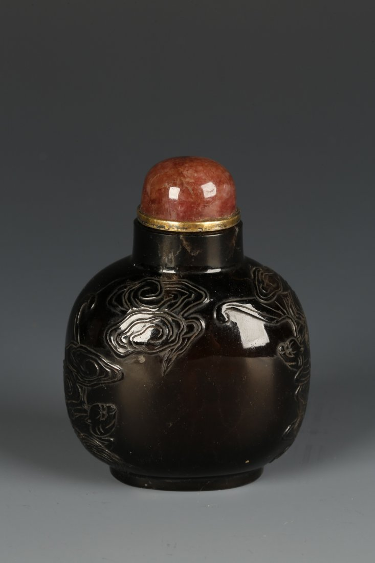 A SMOKY CRYSTAL SNUFF BOTTLE of large bulbous form,