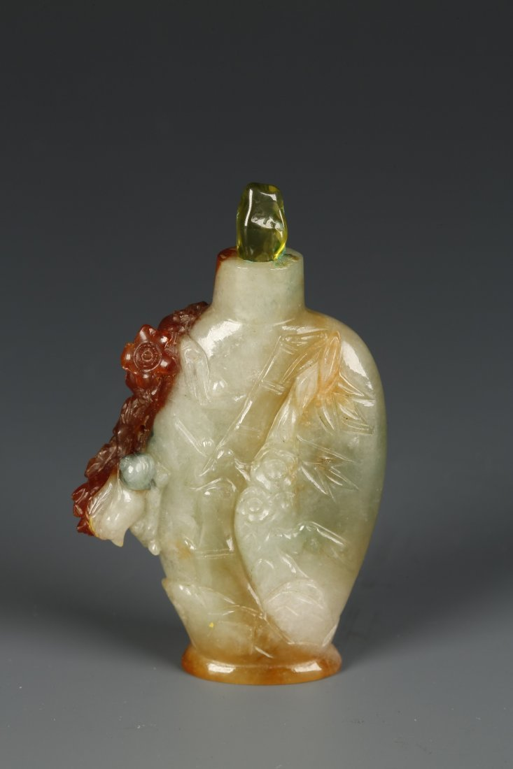 A JADEITE SNUFF BOTTLE of flattened form with a russet