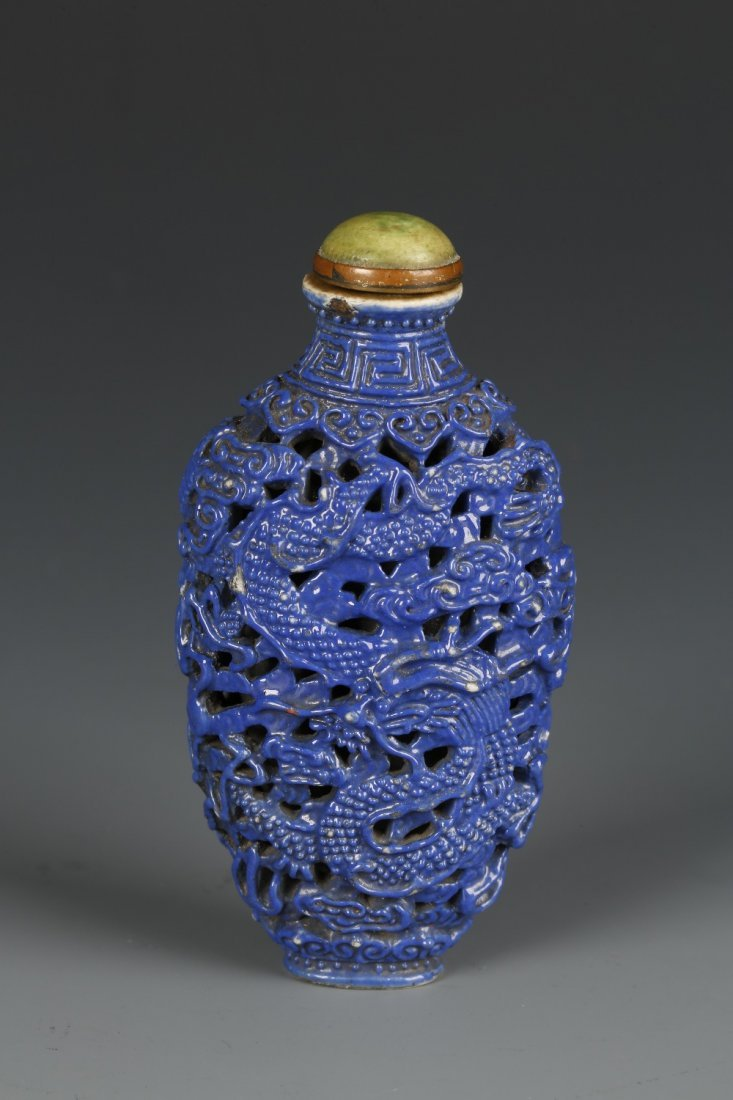 A MOULDED PORCELAIN SNUFF BOTTLE covered in a