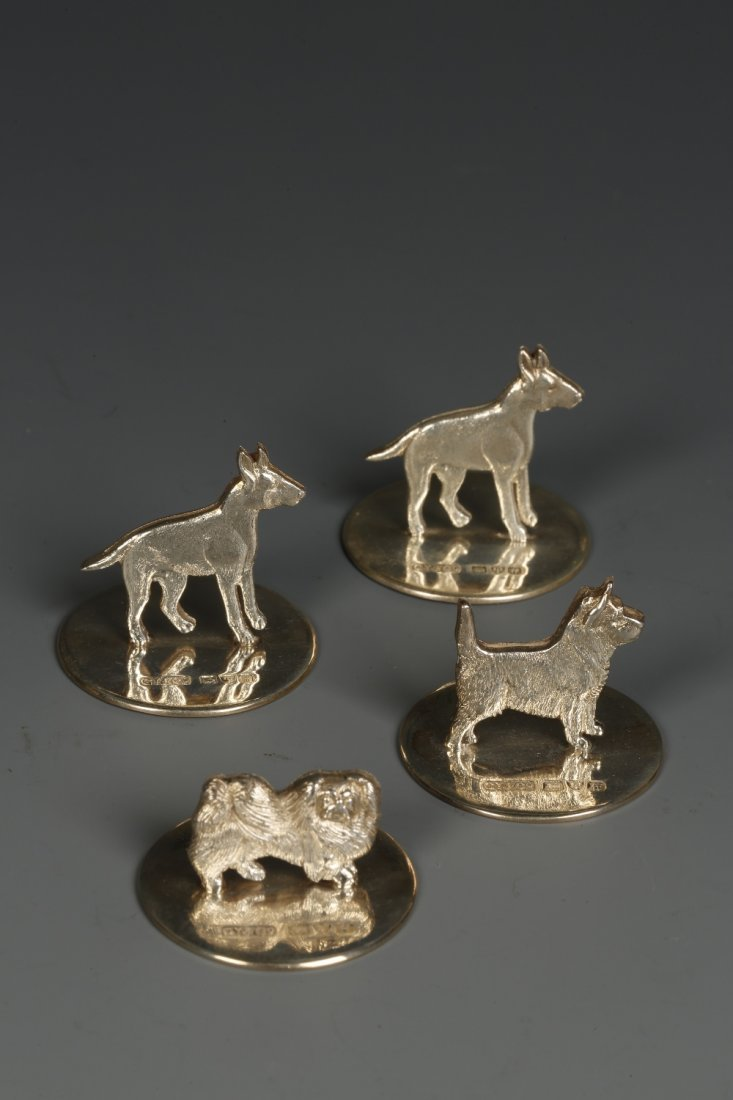 A SET OF FOUR MENU CARD HOLDERS modelled as dogs on