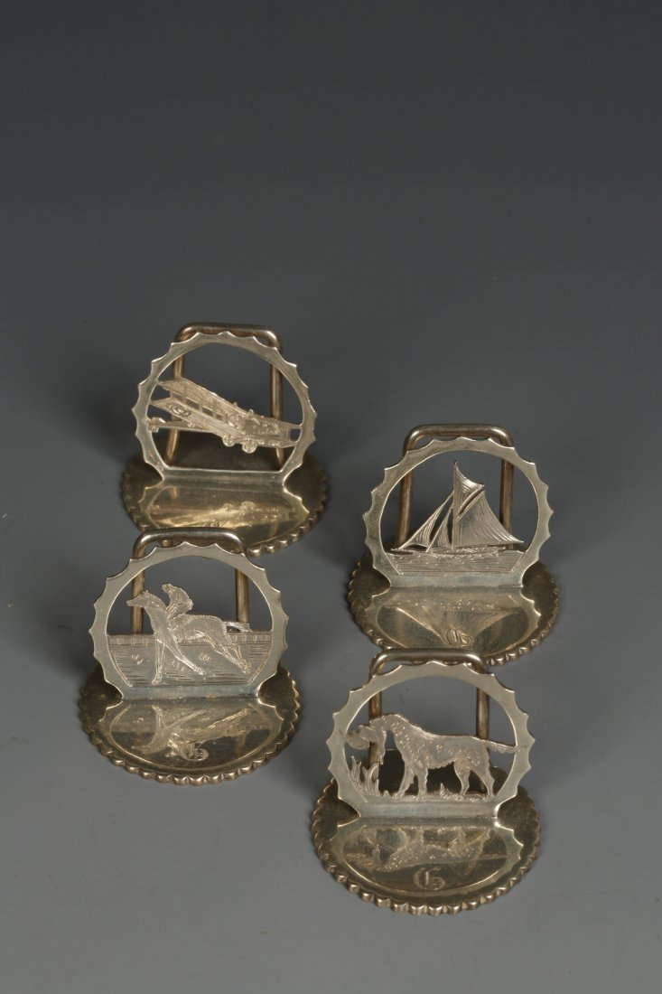 A SET OF FOUR MENU CARD HOLDERS of cut-out circular