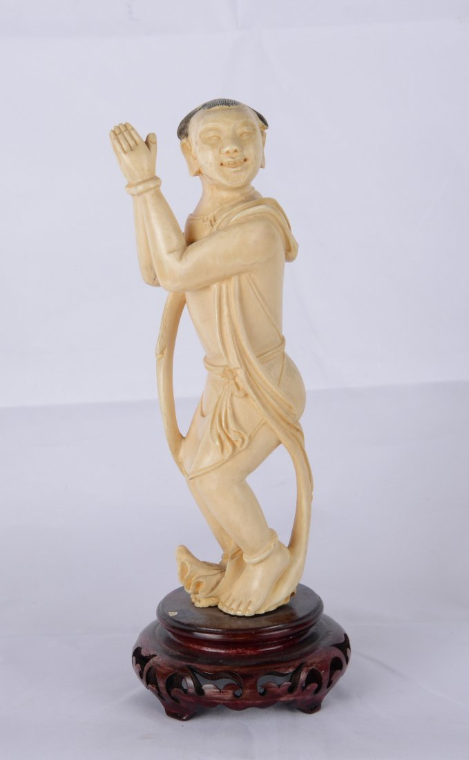 A CARVED IVORY FIGURE OF A CHILD