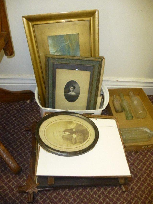 Stack of antique framed pictures.