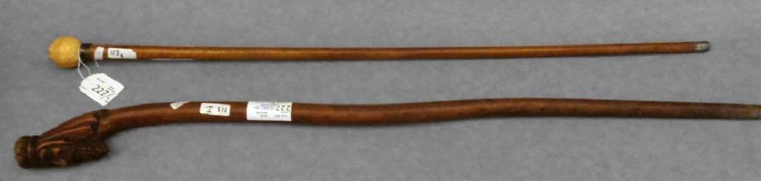 Due bastoni, uno con presa in legno raffigurante