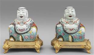 Coppia di Buddha in porcellana policroma, basi in