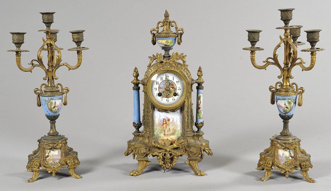 Trittico composto da orologio e due candelieri in