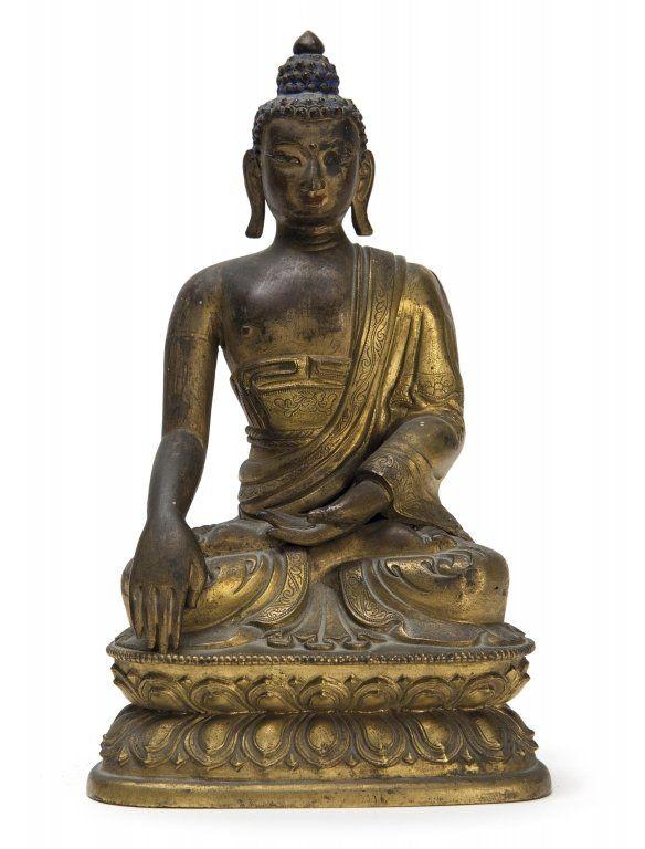 Buddha in bronzo dorato seduto su fiore di loto