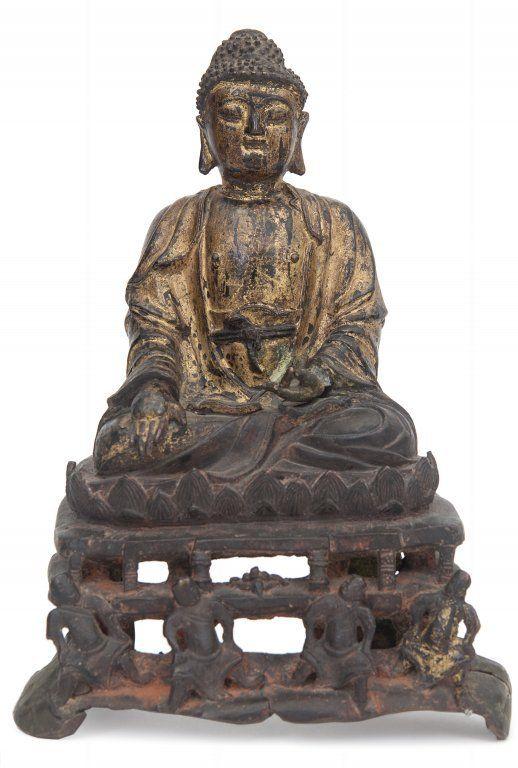 Budda in bronzo dorato seduto su un fiore di loto