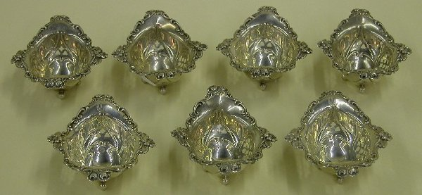 1004: SET OF SEVEN STERLING SILVER FOOTED NUT