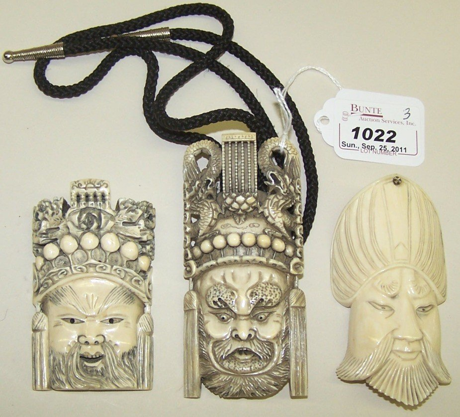 1022: ***THREE CHINESE CARVED IVORY MASK PENDANTS