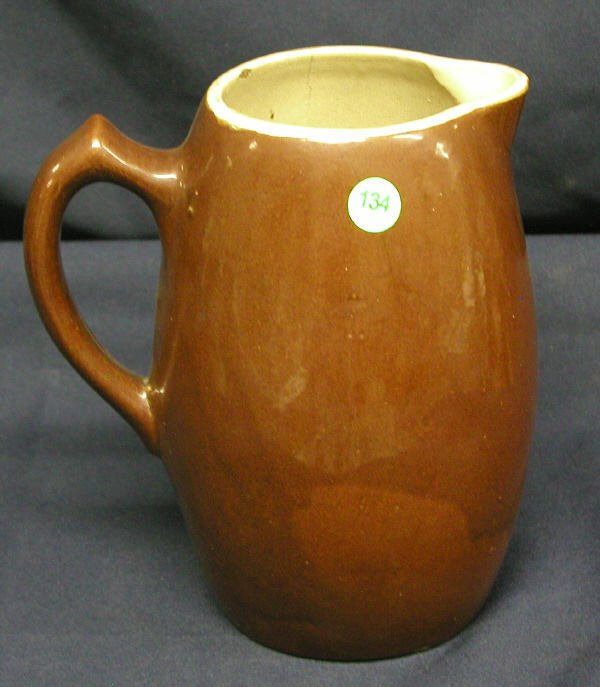 """134: STONEWARE PITCHER BROWN 9""""H, 7.7""""D, .5LB, CHIPS IN"""