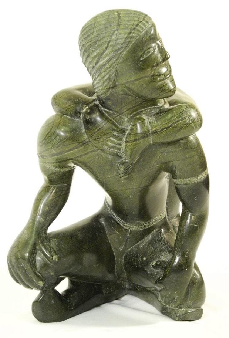 Inuit large soapsone figure group of a kneeling man