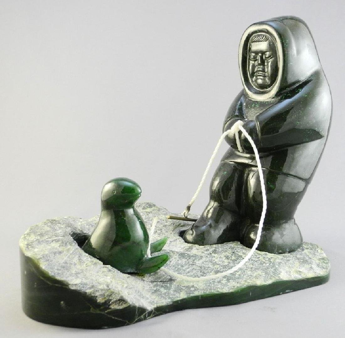 Inuit carved green stone figure group of a standing