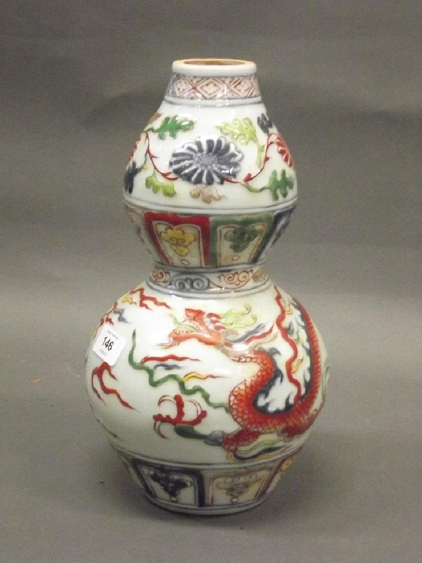 A Chinese earthenware dragon vase with raised enamel