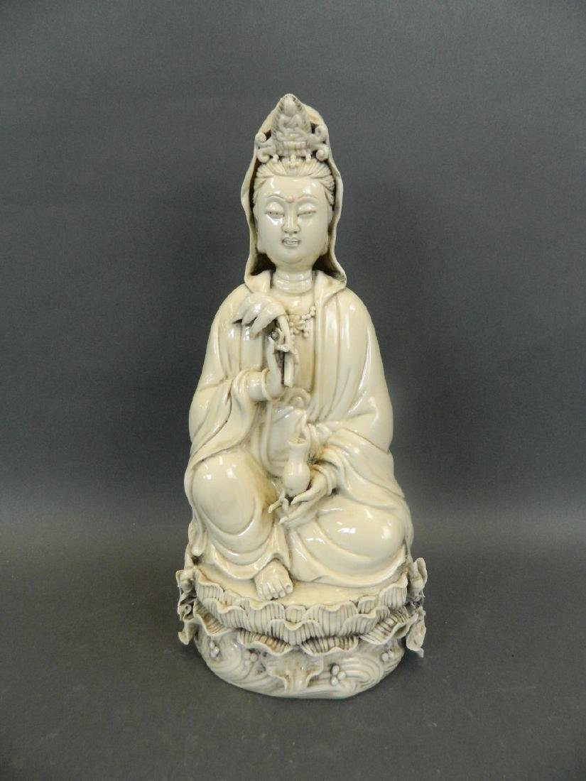 A Chinese Blanc de Chine figure of Quan Yin seated on a